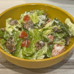 Salad with lettuce, tomato, and bacon in a bowl.