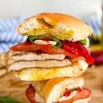 Sandwich with chicken, mozzarella cheese, tomato, and basil next to a whole tomato and some tomato slices.