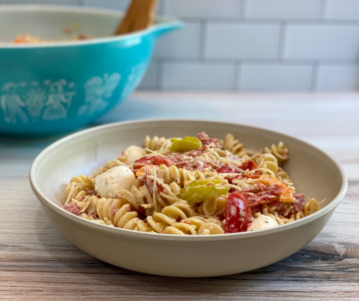 Bowl of pasta salad that contains rotini spiral pasta, fresh mozzarella cheese, parmesan and provolone cheeses, meats, bell pepper, onions, and tomatoes. The bowl is a single serving and sits in front of a serving bowl with the remaining pasta salad.