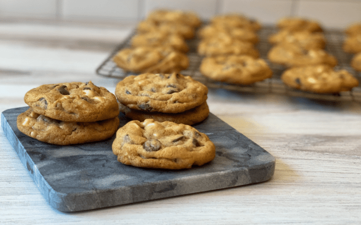 Four cookies on a square plate in front of cookies cooling on a wire cooling rack.