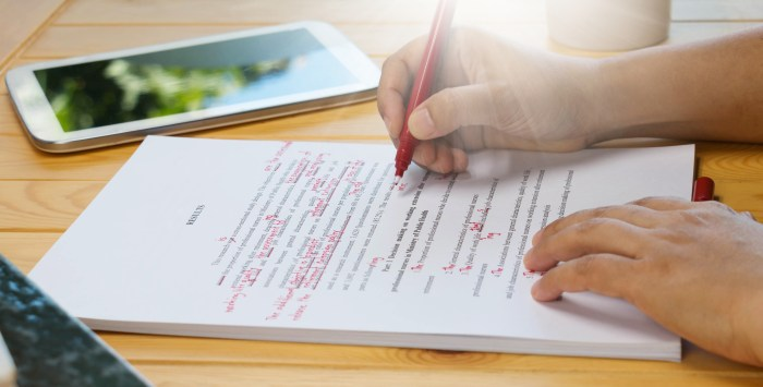 hand holding red pen over proofreading text on table