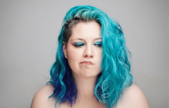 A woman with blue hair and a colorful make-up looks doubtful