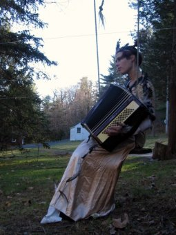 Photograph of Ryder Cooley playing accordion in an antique gown, on a swing, outside.