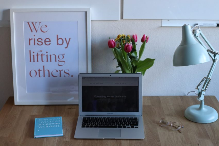 "A neat desk and workspace is decorated with a white metal camera, pink tulips, and a piece of framed graphic art that reads ""We rise by lifting others."" A book and a pair of glasses resting on the blonde desktop on either side of the laptop completes the scene."