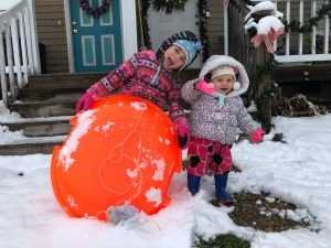 Two little girls, sisters, smile and stand together in the snow with their sled, a big round plastic disk.