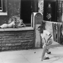 Young black boys play cricket on the pavement in Manchester. Photograph by Shirley Baker Date: 1964