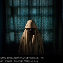 Aisha, age 14, stands for a portrait in Maiduguri, Borno State, Nigeria on Sept. 21, 2017. Aisha was kidnapped by Boko Haram then assigned a suicide bombing mission. After she was strapped with explosives, she found help instead of blowing herself and others up. Photo by Adam Ferguson for The New York Times