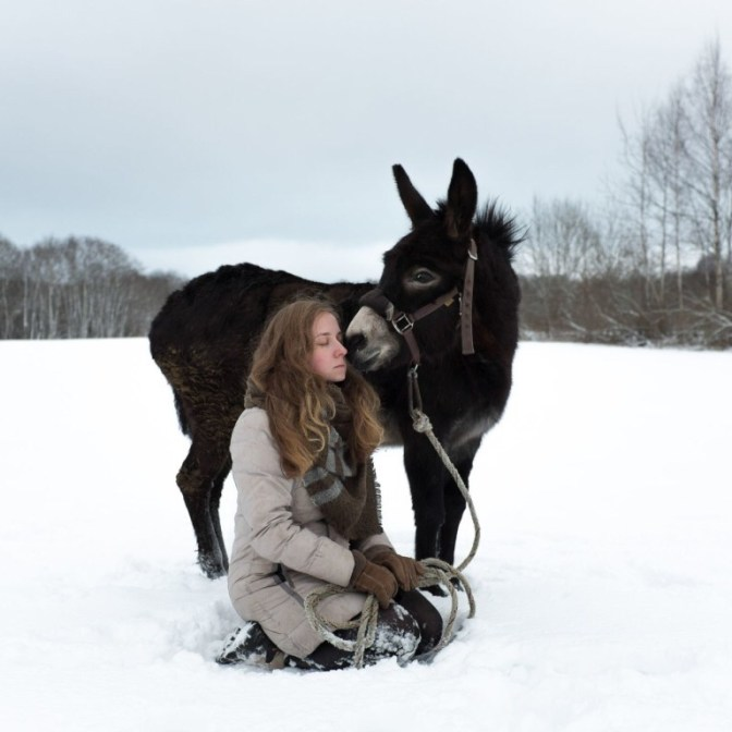 Lisa, a volunteer, with a donkey on a walk. She has been at Svetlana Village for nearly two years. She worked in the bakery, took care of the donkey and now is working on the farm. Young people from different countries often come to live and work in the village.