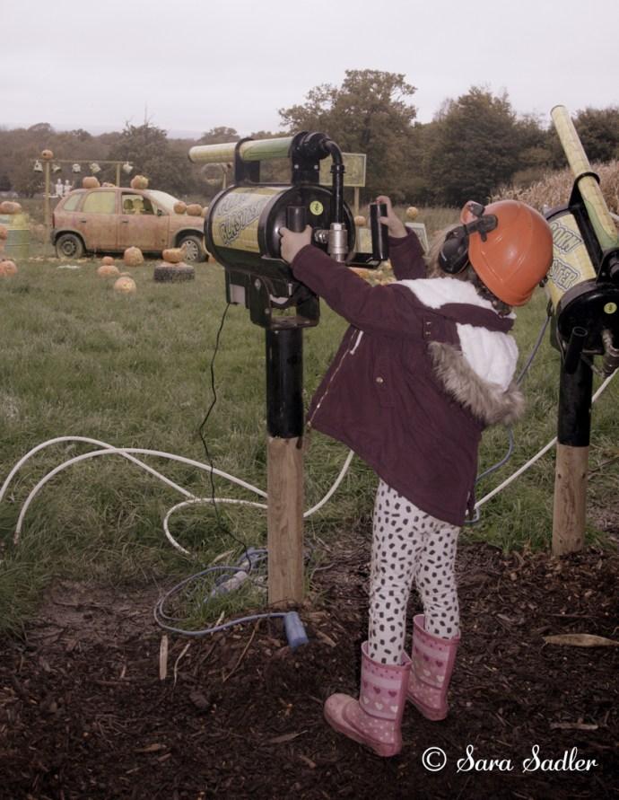 Small child shooting corn at pumpins!