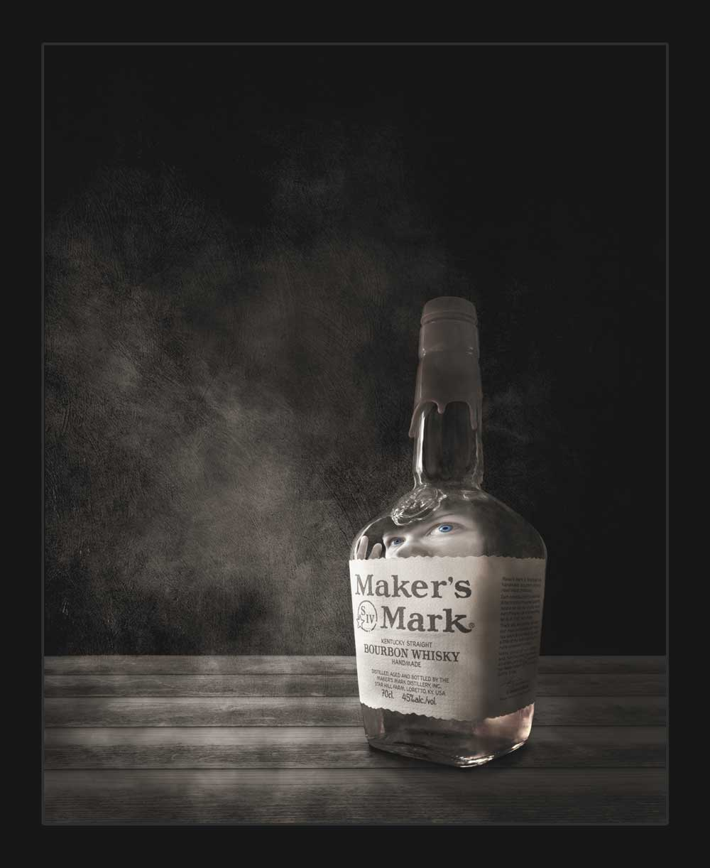 Creepy fine art image of a person trapped in a bottle of whisky. Created during the 2020 lockdown
