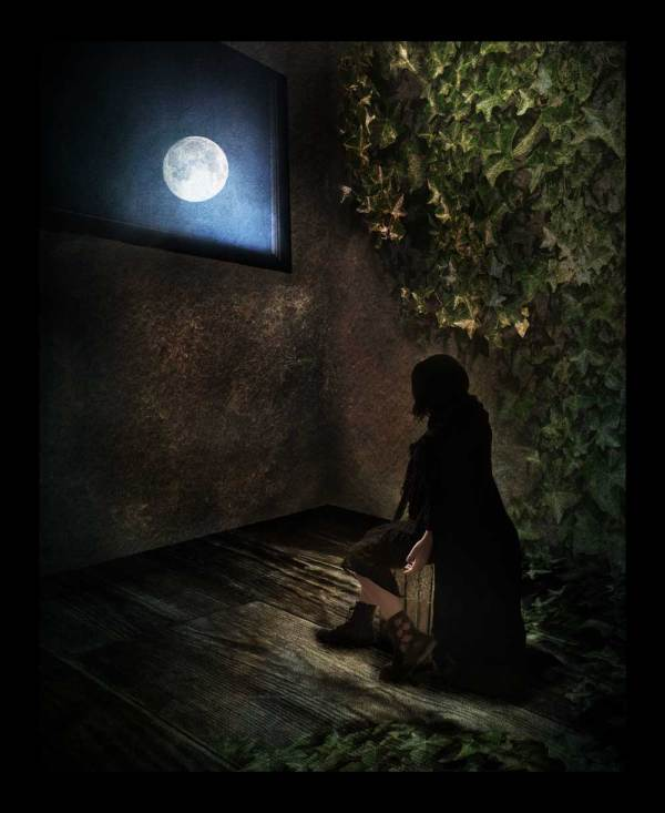 A lady sits in a dark creepy room staring out the window to the moon.