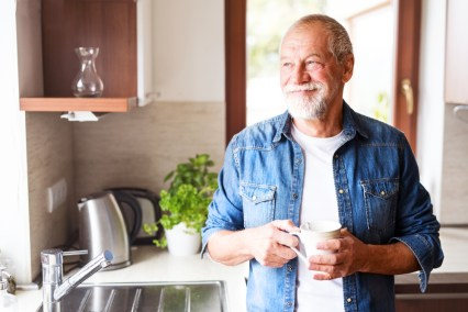 Healthy older man smiling and holding mug in the kitchen