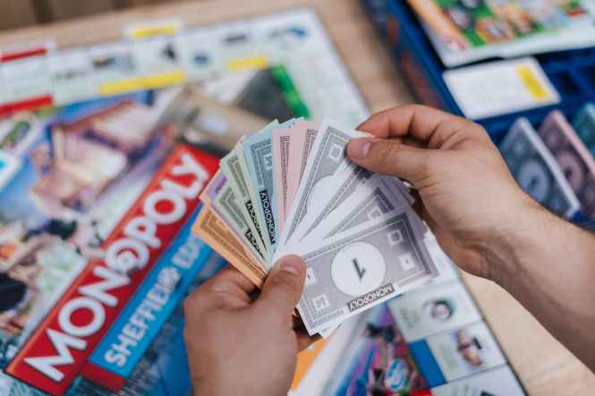 faceless player with fake banknotes playing table game