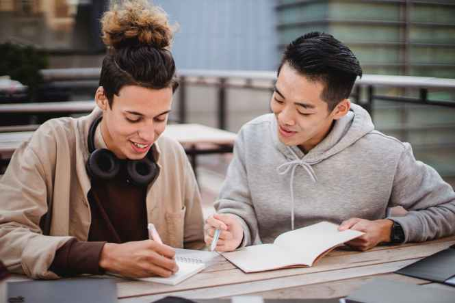 multiracial male friends writing information in notebooks on table