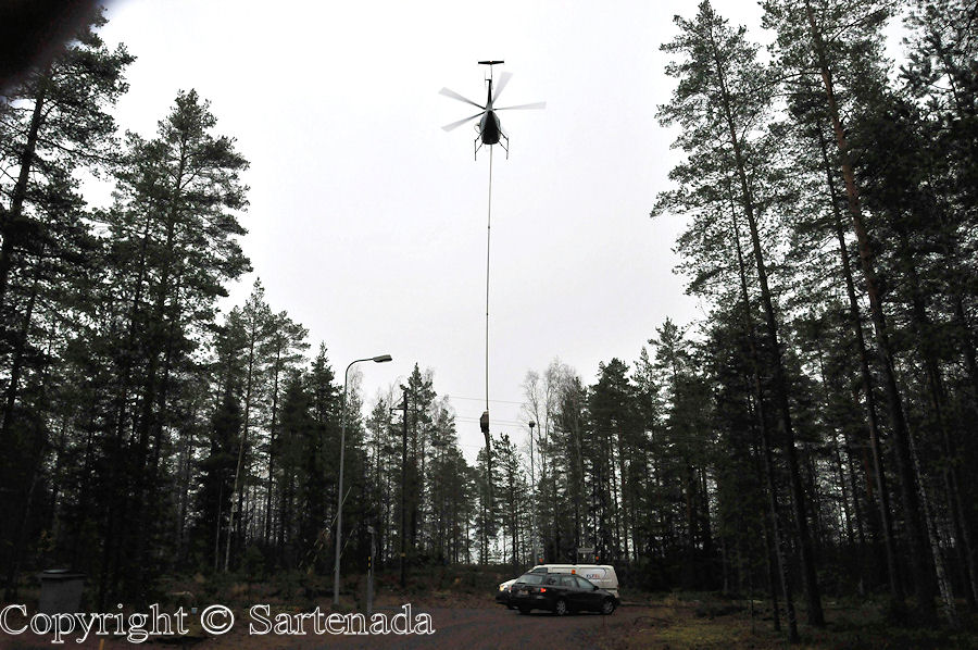 Helicopter cutting branches from electric lines