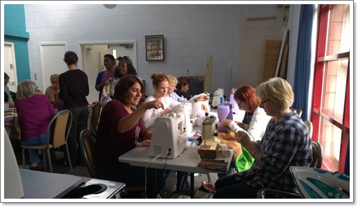 """ And here we have Silvia, Selena, Mary, Faith, Elna & Alison studiously working with the sewing machines while the patchwork team chat & sew behind them!! A hive of industry and creativity!"""