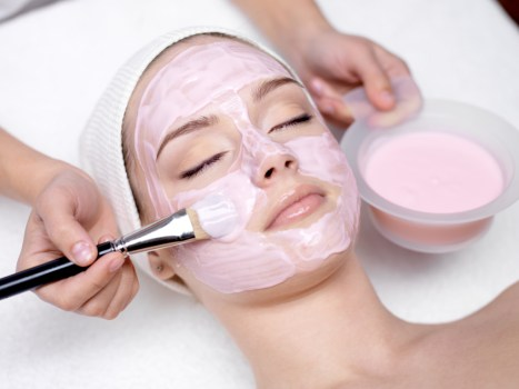 Young beautiful girl receiving pink facial mask in spa beauty salon - indoors - pores open close a myth