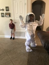 The boys think Daddy's bee suit is fun.