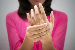 Eine Frau die aufgrund erhöhter Harnsäure Schmerzen von Gicht hat