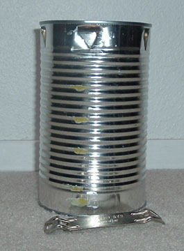 5. Turn the 3-pound coffee can upside down. Use the can opener to punch triangular holes at intervals below the bottom of the can, which has of course now become the top of the can. The holes at the stove's top will allow oxygen to feed the lighted burner below. The holes don't show up well on the dark coffee can, so we're using a juice can here to illustrate.
