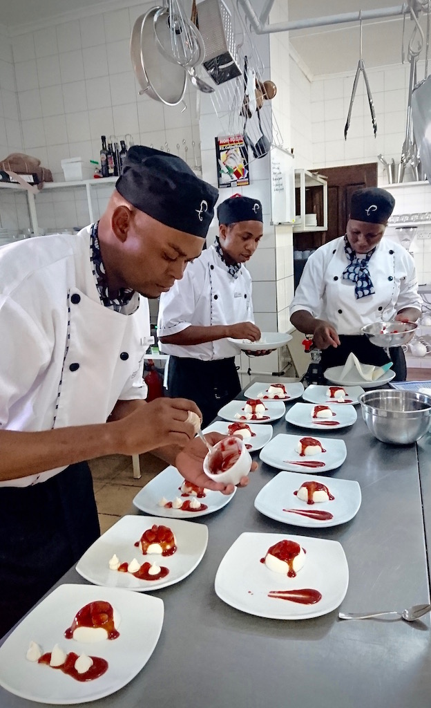 The Elephant Café chefs preparing the Munkoyo Panna Cotta with Seasonal Strawberries & Baby Meringues.