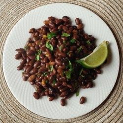 Mexican style black soybeans with cilantro and a lime wedge on a white plate.