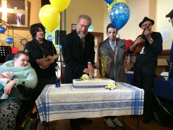 """Mayor Callow"" cuts the cake, assisted by Ballarat Ukulele Kollective members, Vicki Maree Barnett & Gary Mann, and watched by Koby Bunny (who also live-streamed much of the event.)"