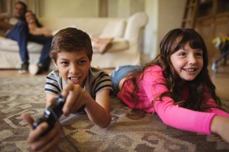 Siblings lying on rug and playing video game
