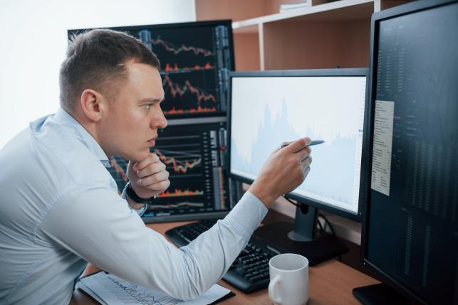 Checks information. Man working online in the office with multiple computer screens in index charts
