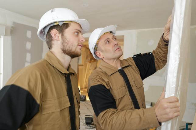 constructor and apprentice verifies correct installation on garage door panel