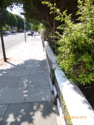 No benches, but a few garden walls in the shade of a Goldstone Villas tree