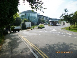 Entrance into the important City Park office complex employing 2,000. Droveway drops steeply down where the vehicle can be seen going.