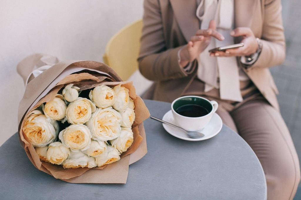 woman sitting at the round table with flowers and a cup of coffee and looking at her mobile phone