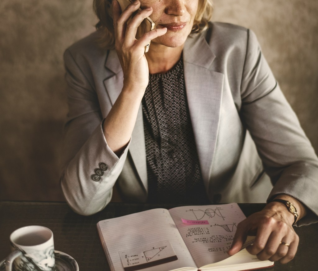 a woman talking on a mobile device sitting at the table with a business notebook