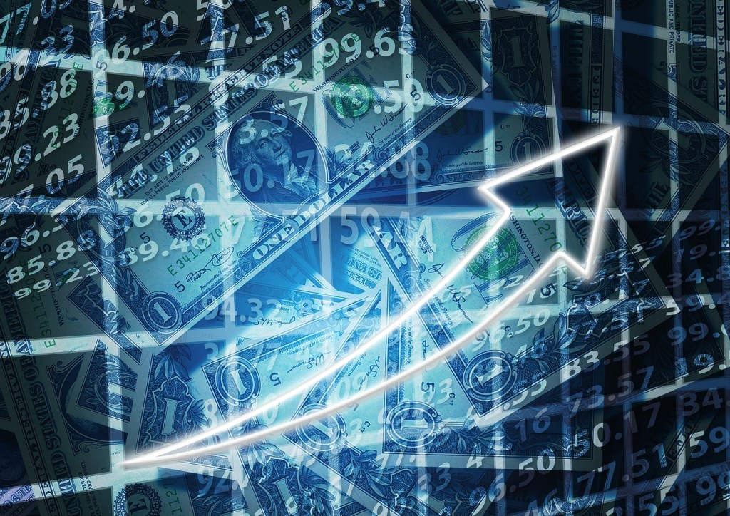 A screen showing images of stock market numbers, american dollar banknotes and an arrow
