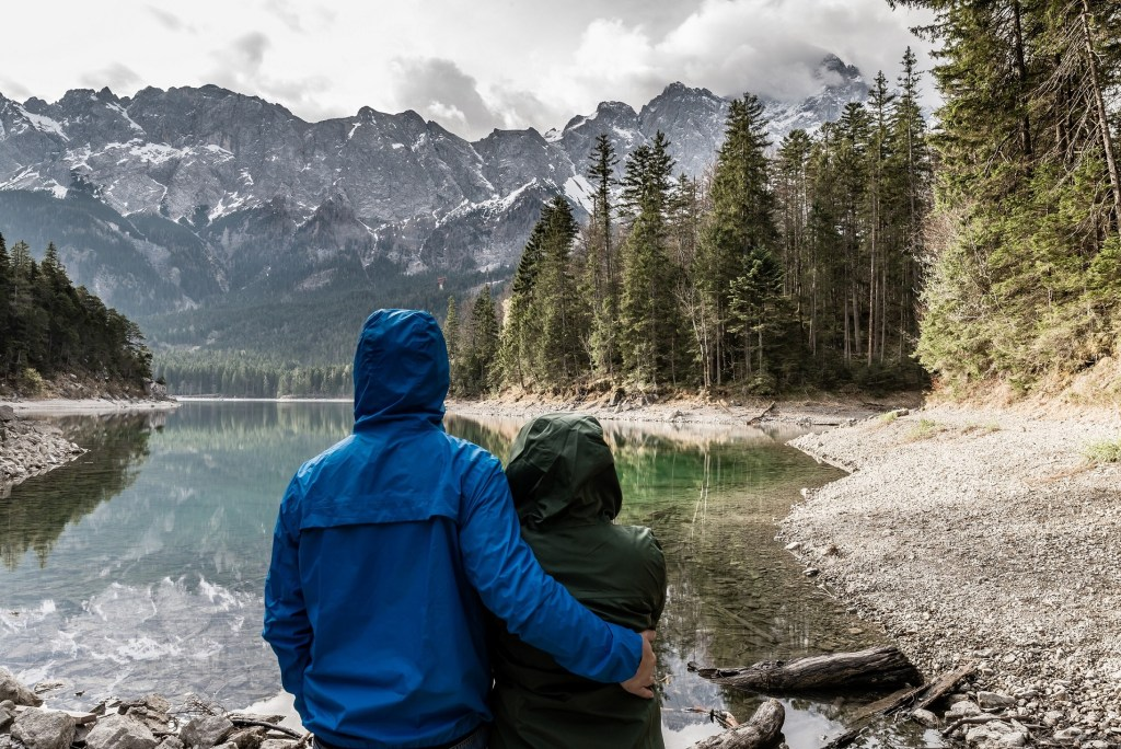 a couple in their light jackets looking at the scenic view of  a small lake surrounded by forest and mountains