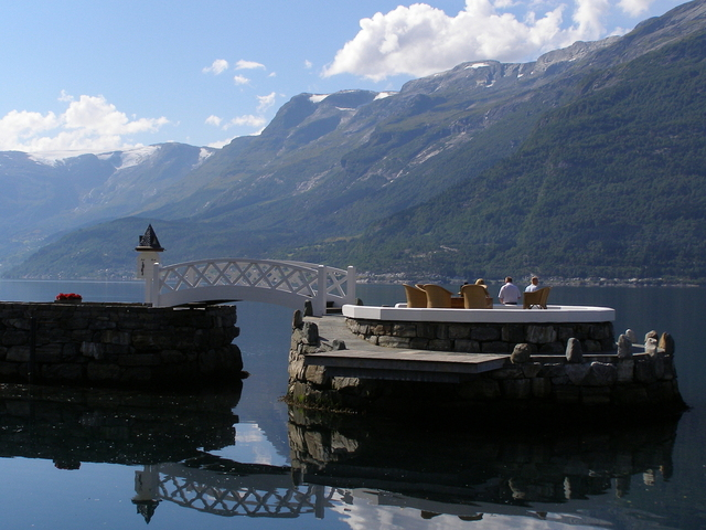 a group of retirees sitting on the deck in the middle of the mountain lake with a scenic view