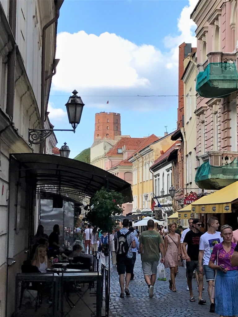 People are walking along cobblestone Pilis St. in Vilnius'Old Town