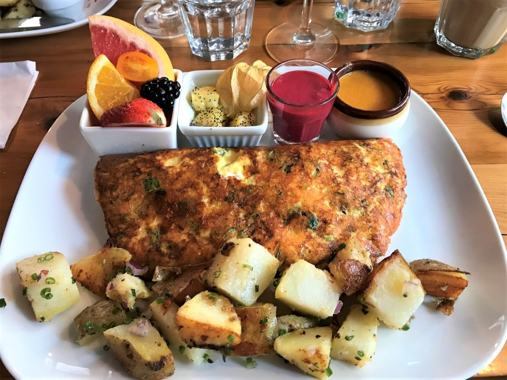 brunch plate with omelette, potatoes, fruits