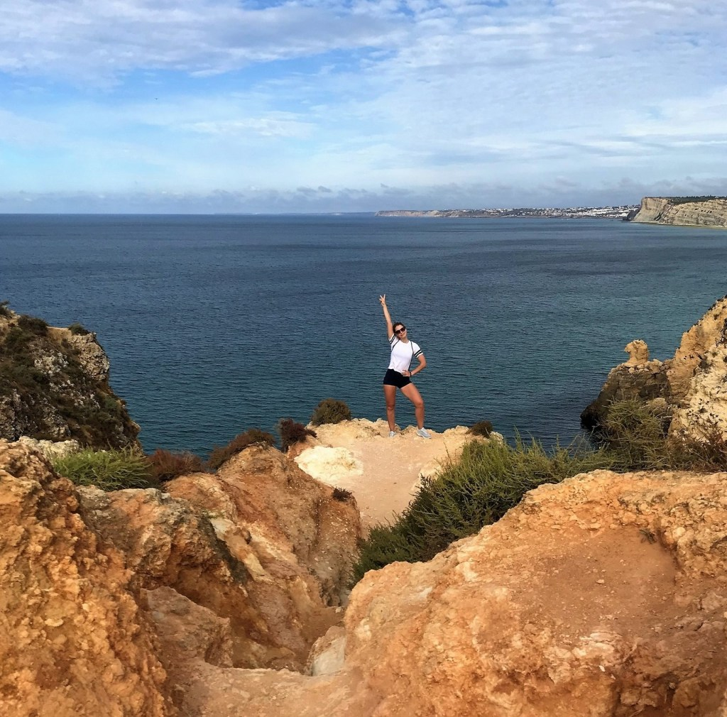 A woman standing on top of rock-achieving goals