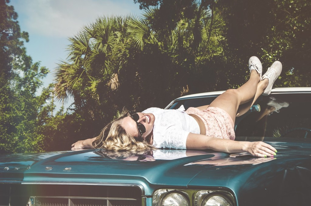 boomer woman laying on top of the car surrounded by palm trees