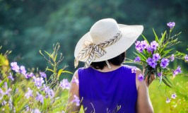 woman in purple dress with field flowers - smooth transition to retirement