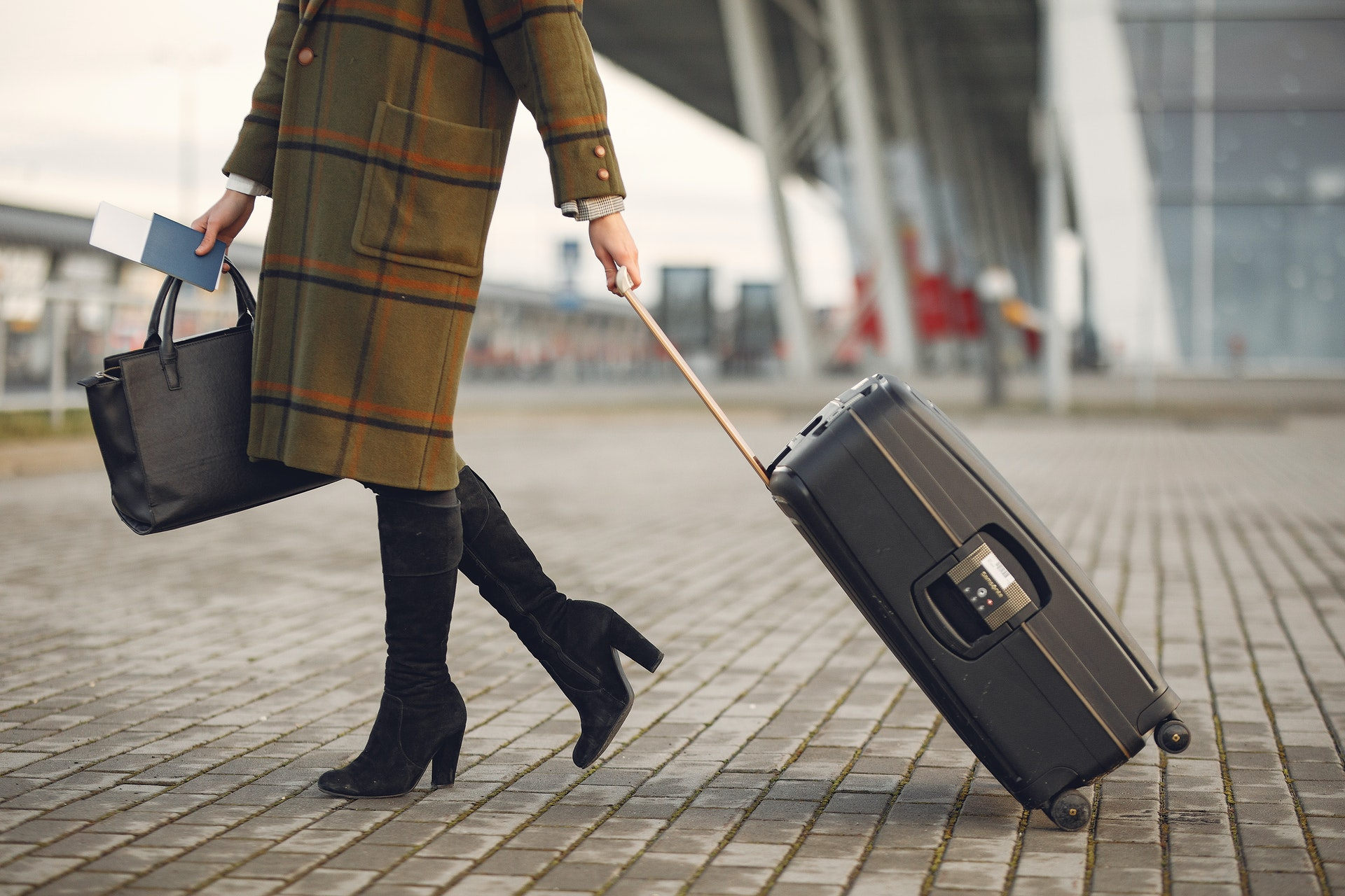 woman in boots with luggage bag - retirement travel tips