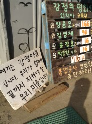 """This is Gangjeong Village. Together, we will defend our village until the end."" On the right, imprisoned activists and their days in prison are displayed."