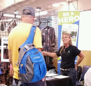 Amber Simmons with Saving Sight speaks with a gentleman at the Kansas State Fair about donor designation.