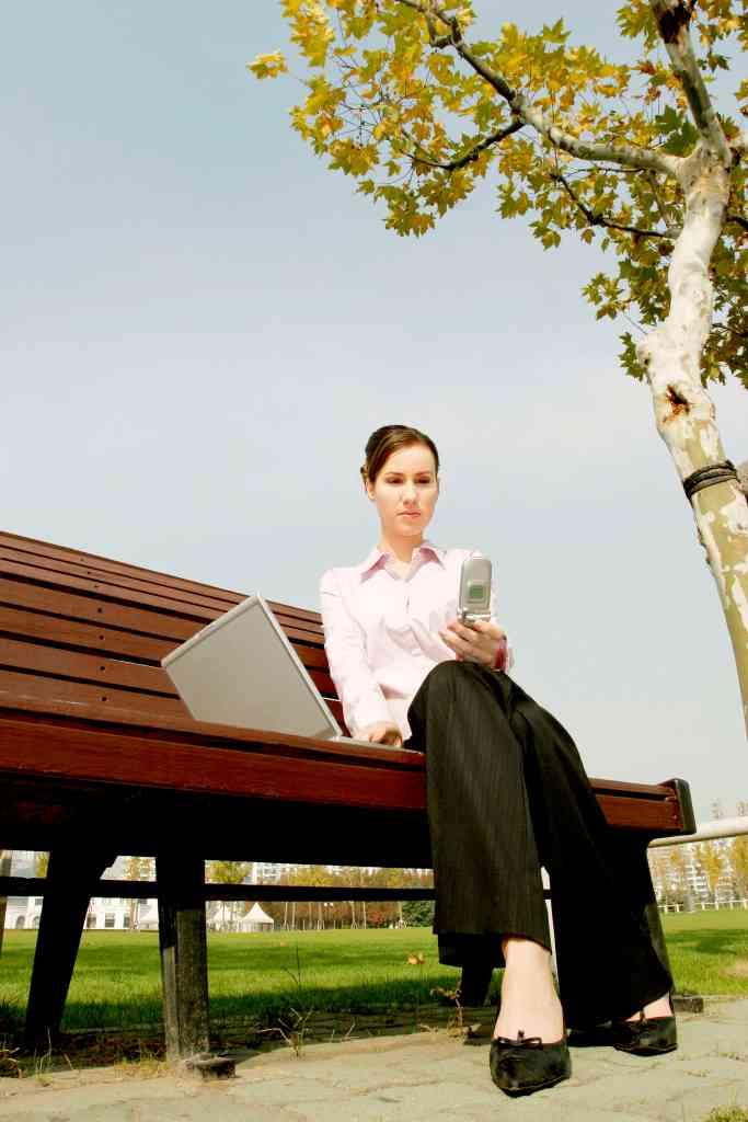 upcoming work trends - woman working remotely on a park bench with cell phone and laptop