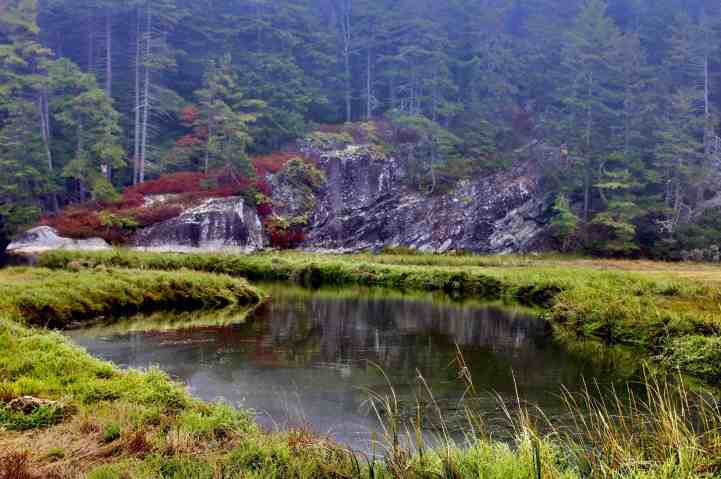 Granite rock formations reflected in a river seen while hiking in Maine.