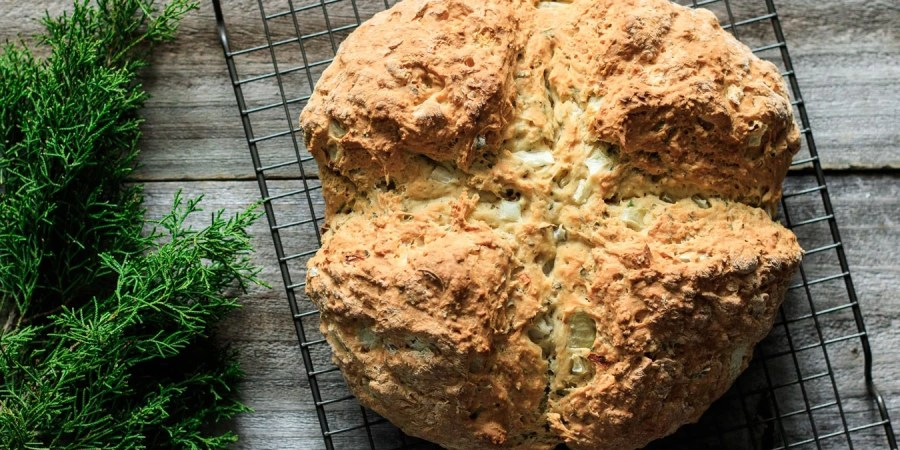 Oregano Onion Soda Bread: this easy recipe for a loaf of moist, savory Irish soda bread is sure to be a hit on St. Patrick's Day. This no yeast white bread is quick to make for dinner, and uses buttermilk and baking soda to make it rise. No machine is required to mix up this dough! | www.savortheflavour.com #sodabread #stpatricksday #irish #savory #recipes