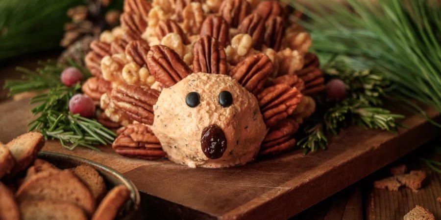 closeup of woodland hedgehog cheese ball with rosemary sprigs, pine branches, and a bowl of crackers