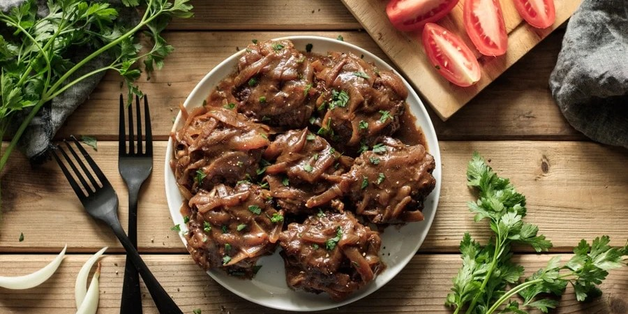 plate of Salisbury steak with two black forks, fresh parsley, onion, and sliced tomatoes